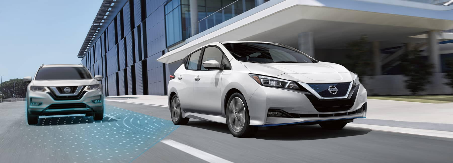 A 2021 White Nissan Leaf driving by an office building_mobile