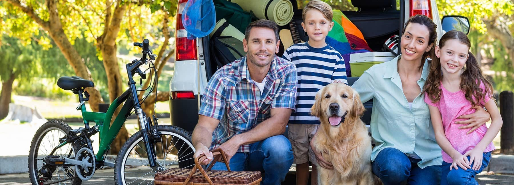 Smiling family crouching in front of their packed car