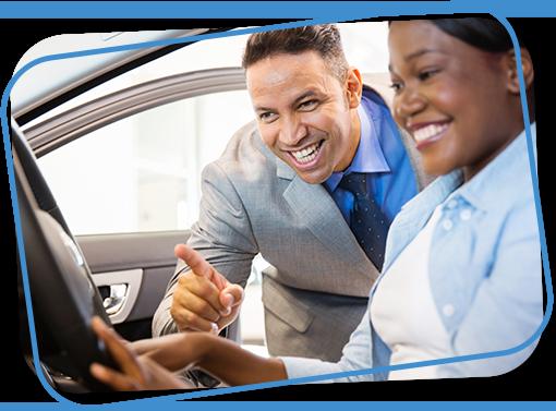 car salesman showing customer inside a new car