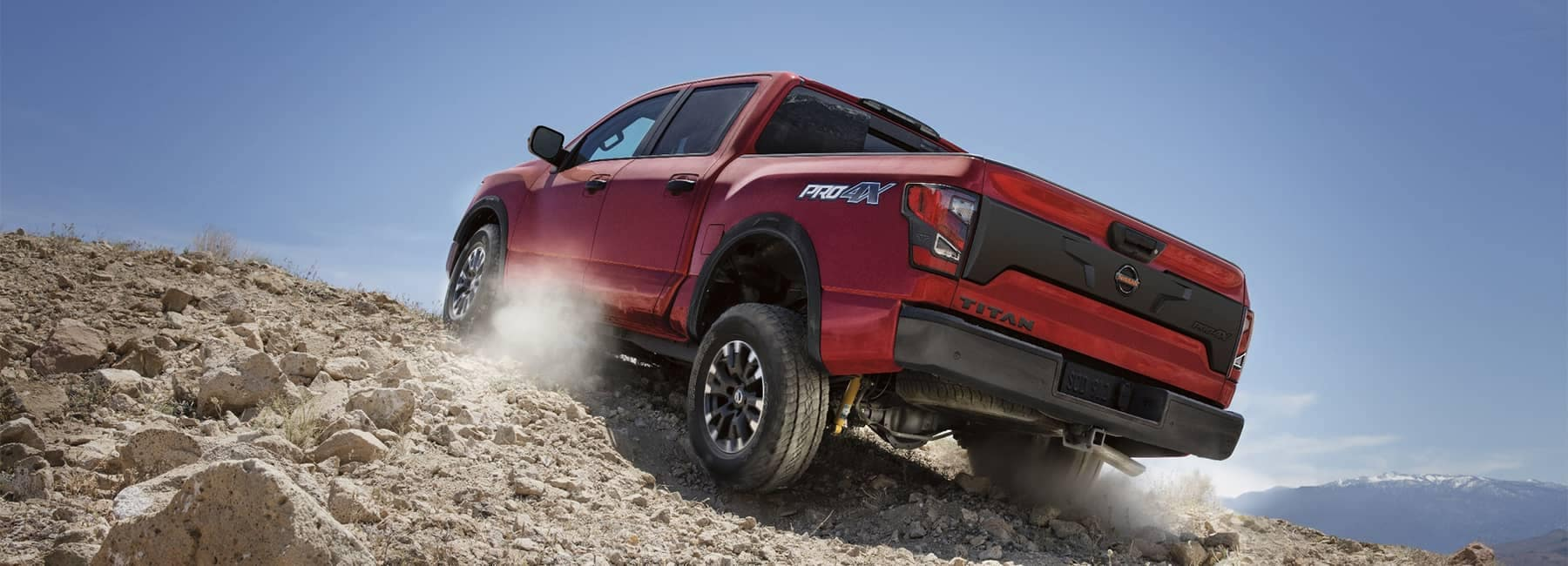 Rearview of a 2021 Red Nissan Titan truck driving up rocky terrain