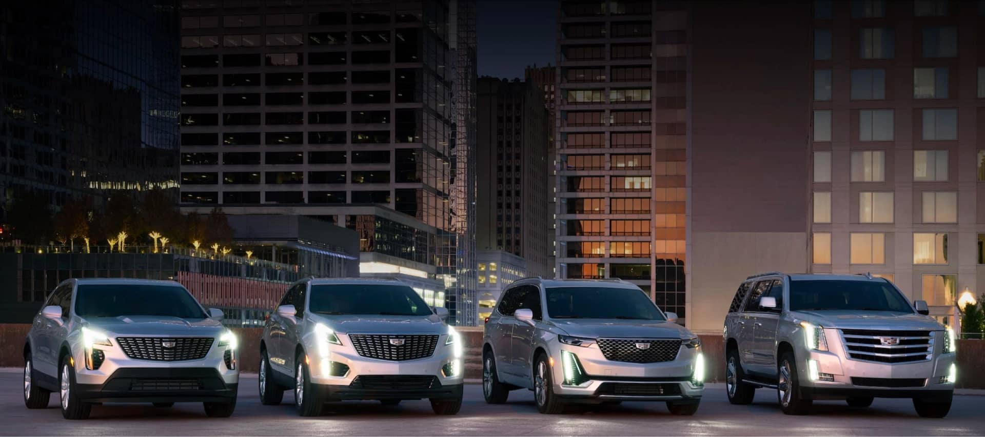 Cadillac vehicles parked in city at night