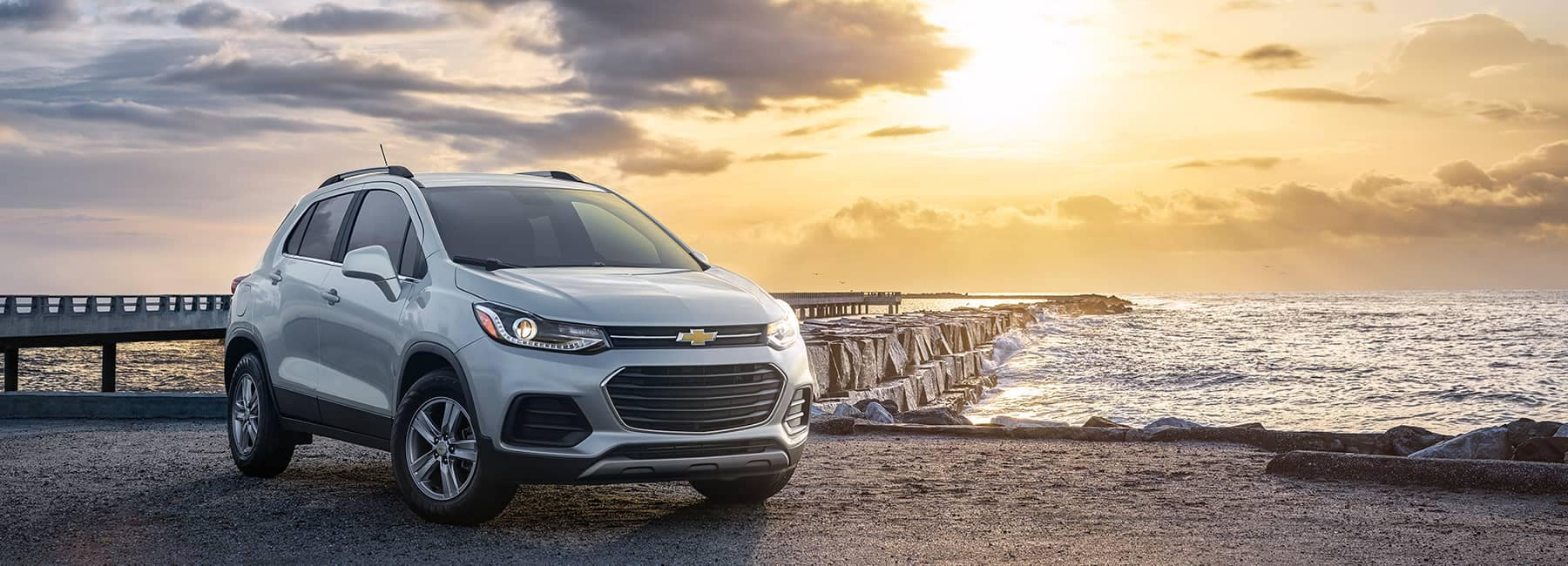 White 2021 Chevrolet Trax parked in front of an ocean pier