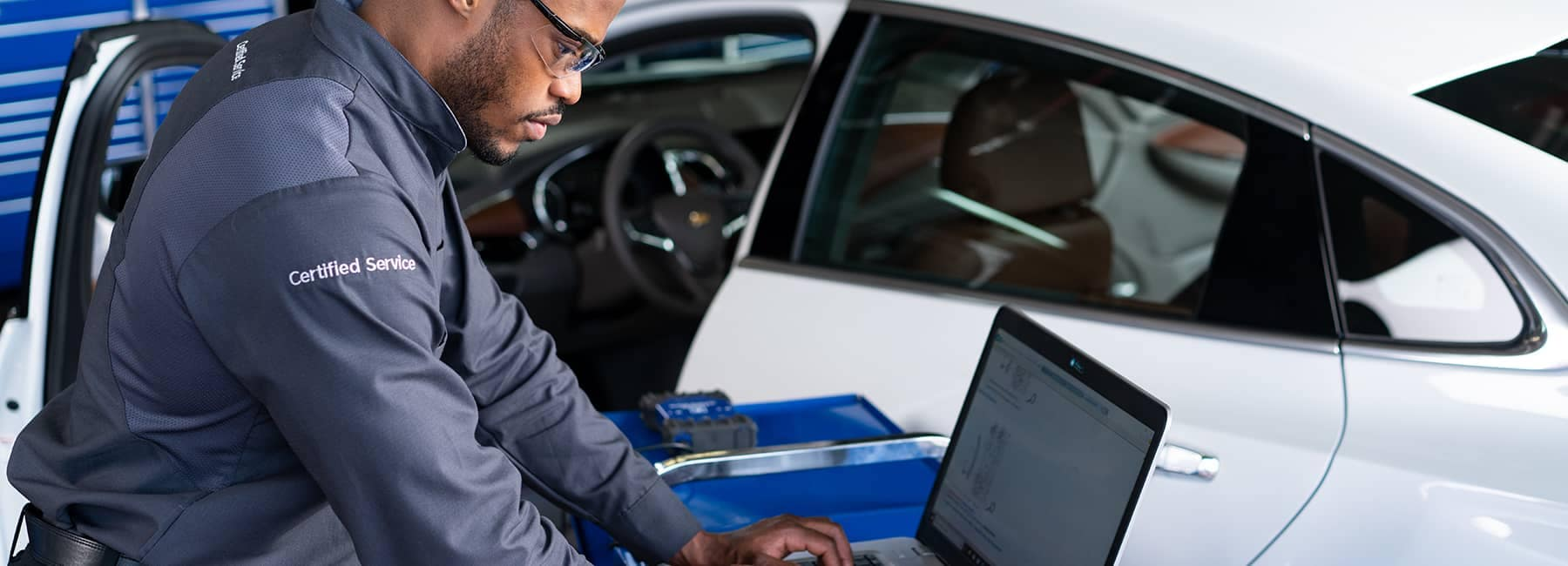 Chevrolet service technician looking at laptop