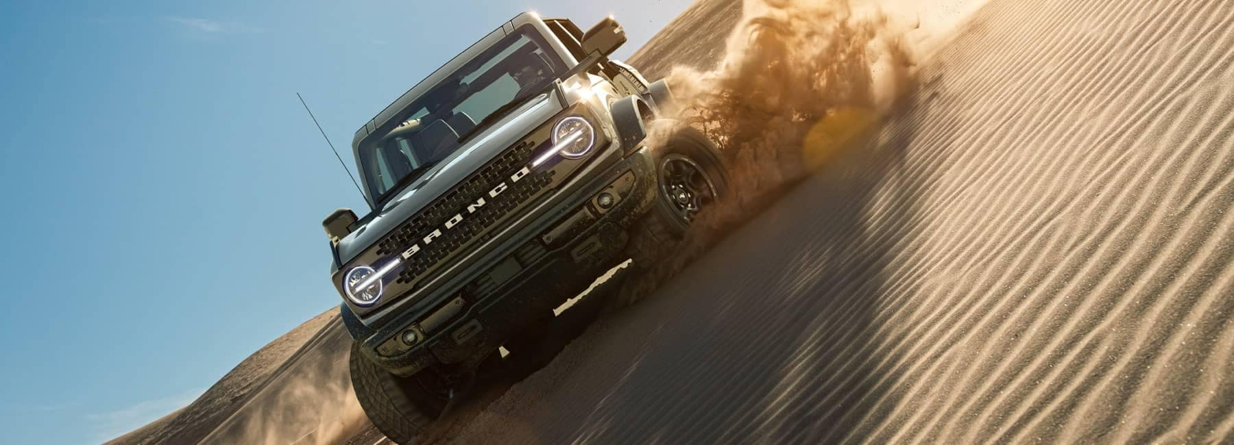 2021 Ford Bronco in Cactus Gray being driven on a sand dune