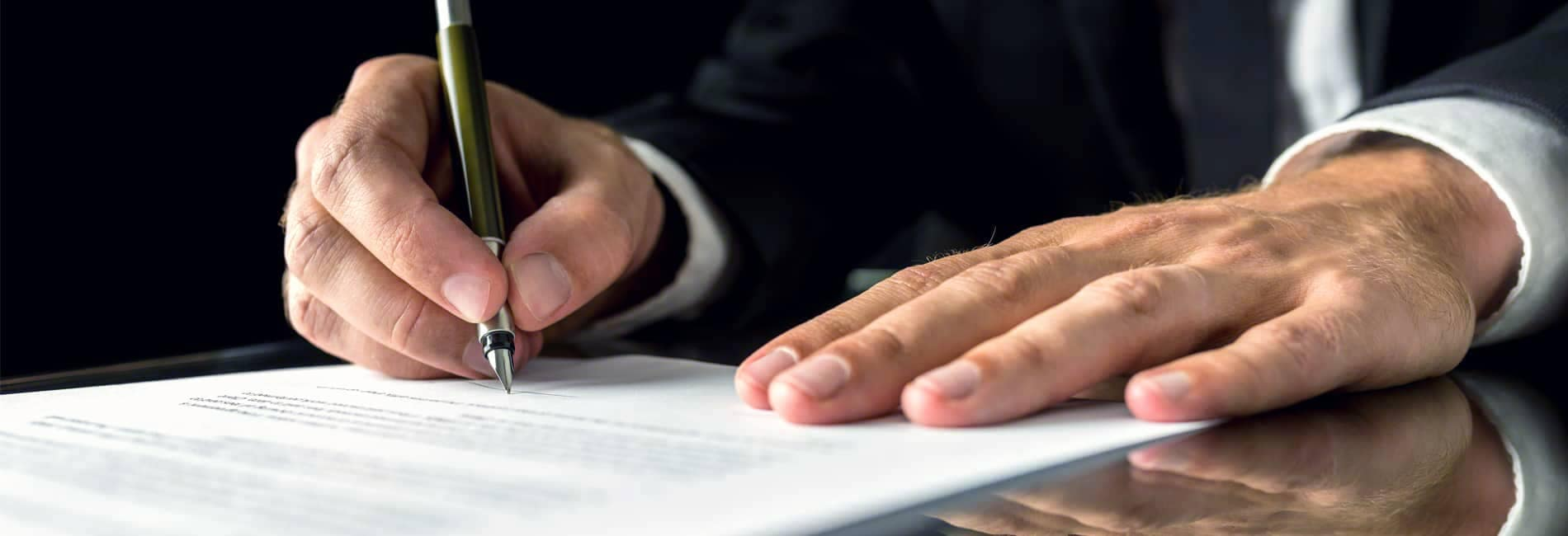 Hands of Man in Suit Signing Document