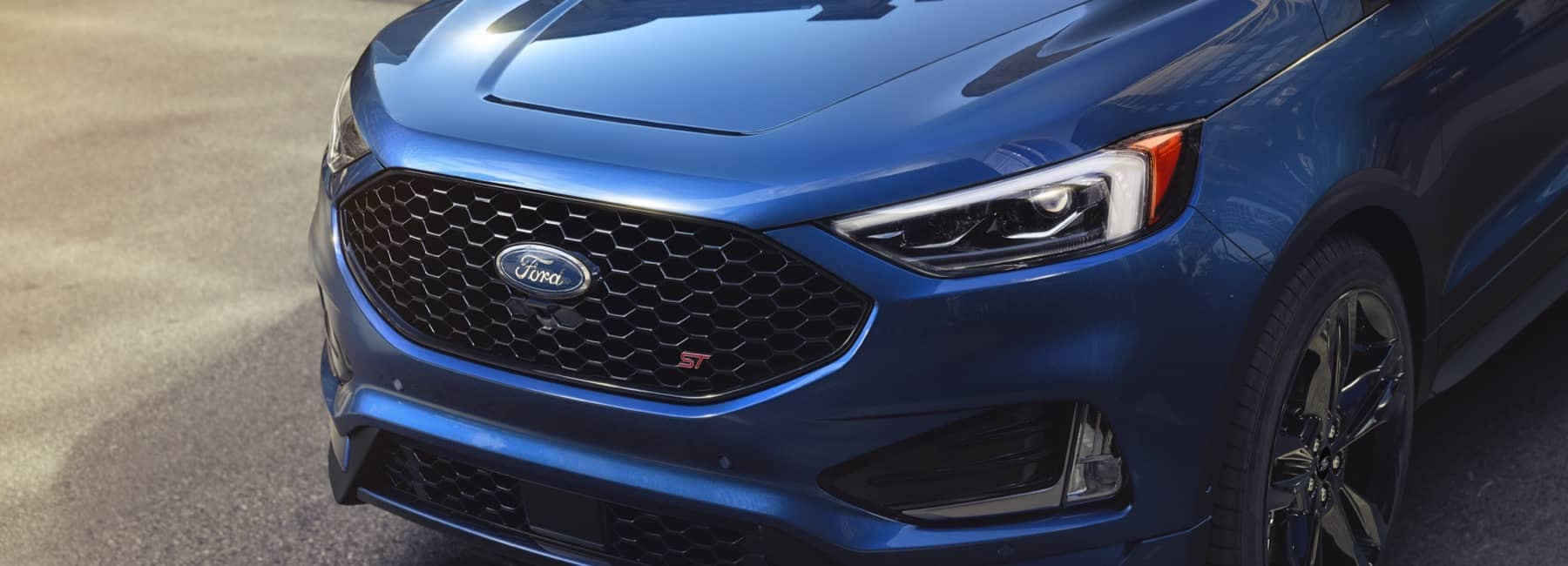 Man walking toward a parked 2021 Ford Edge in Ford Performance Blue