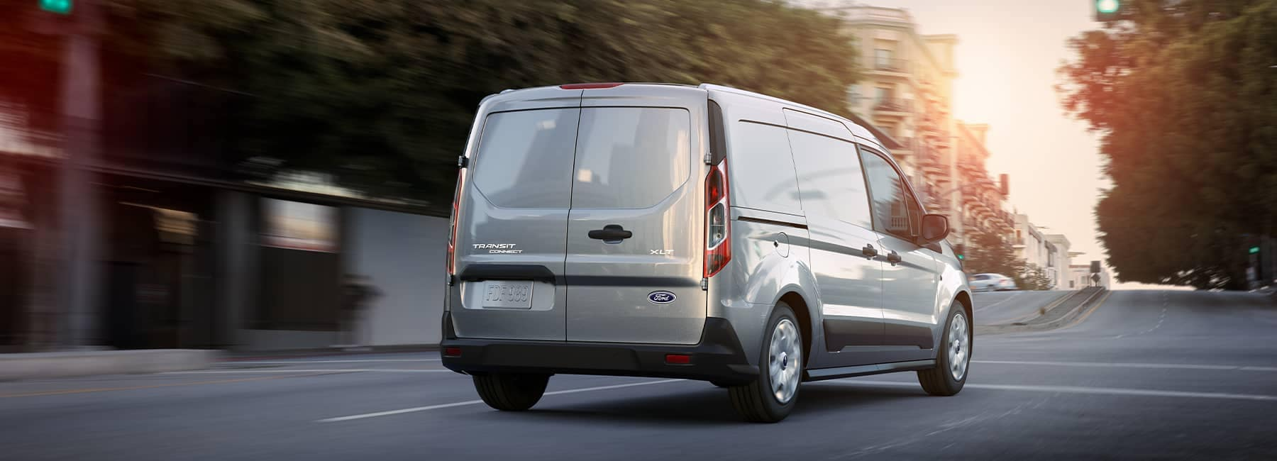 White 2021 Ford Transit driving away on a suburban street