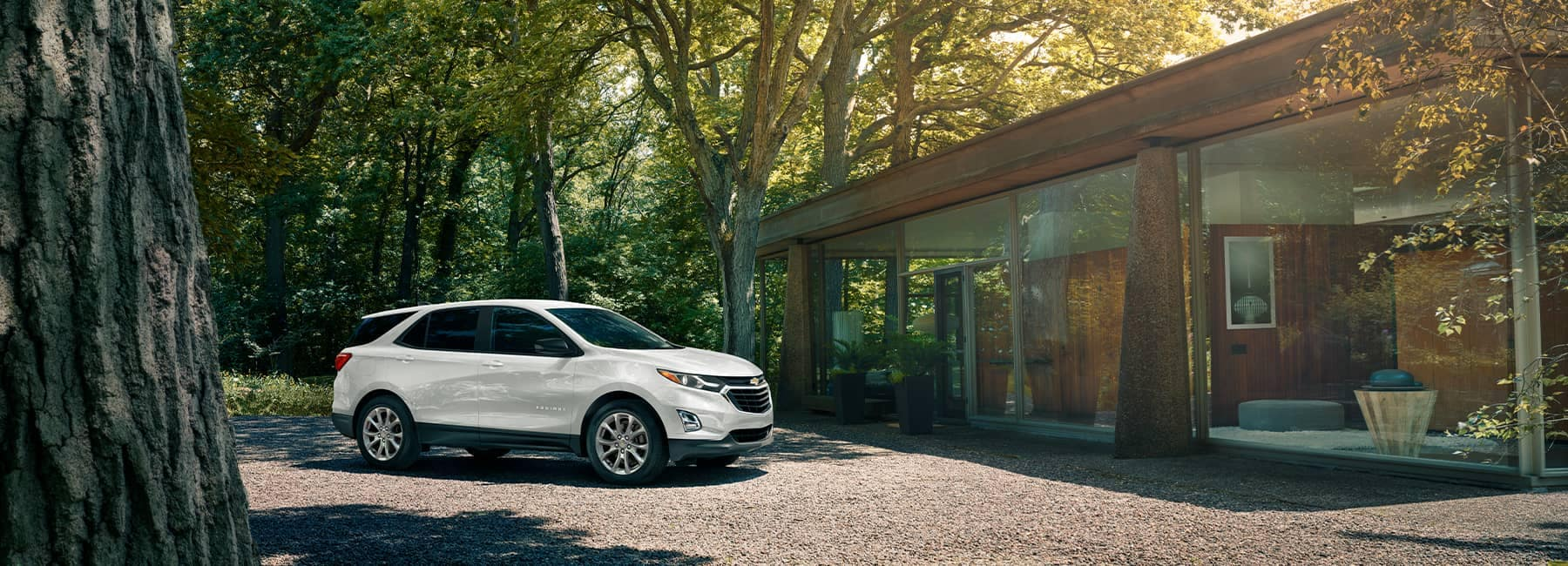 A White 2021 Chevrolet Equinox parked in front of a modern house tucked in the woods