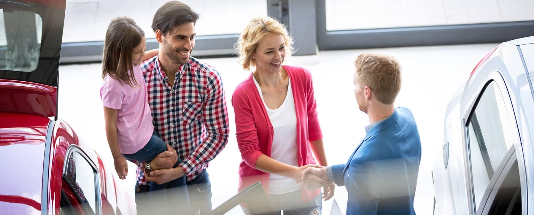 Family at dealership talking to salesperson