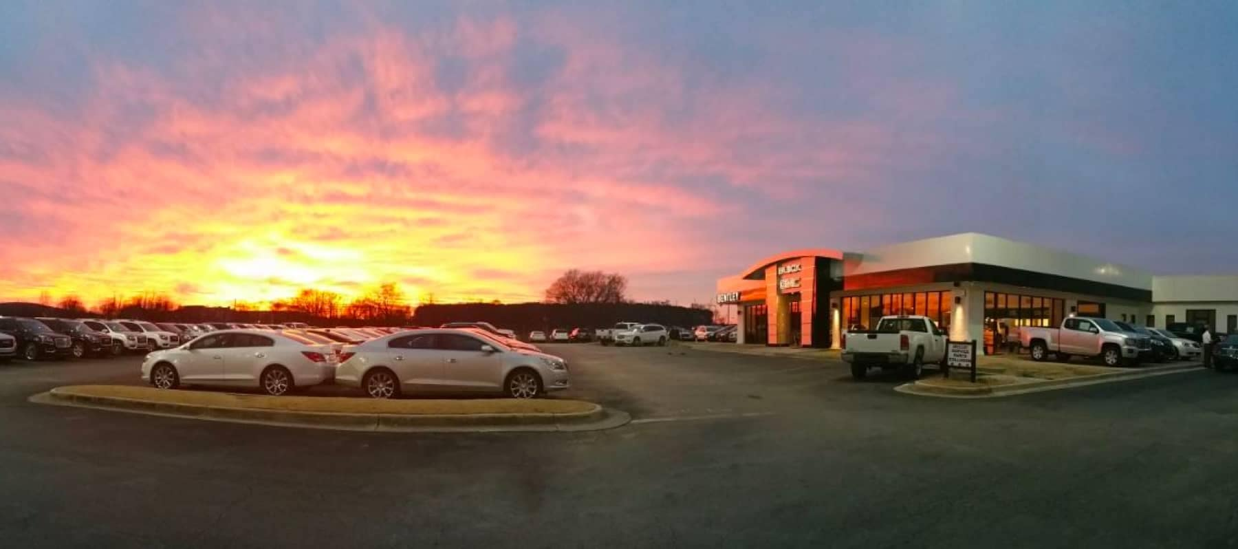 exterior view of dealership with sun setting in the distance