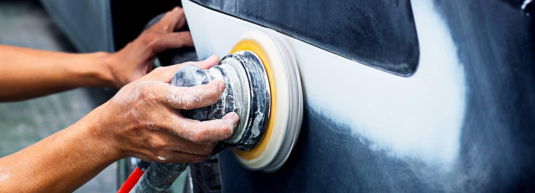 Body shop technician sands down car body