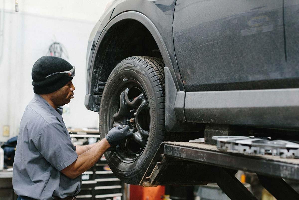 Service technician removes car tire bolts
