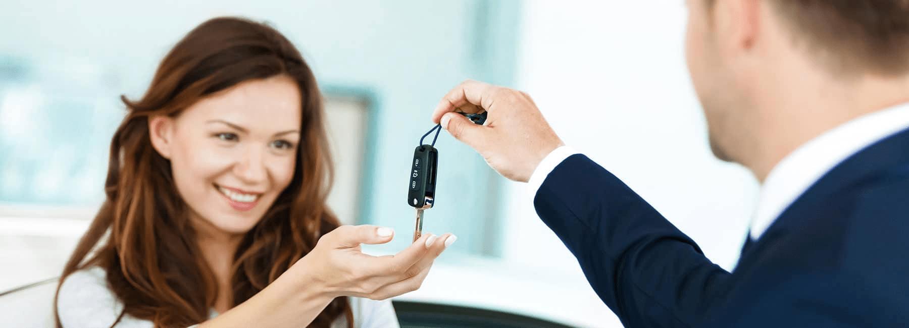 happy woman receives car keys from car dealer