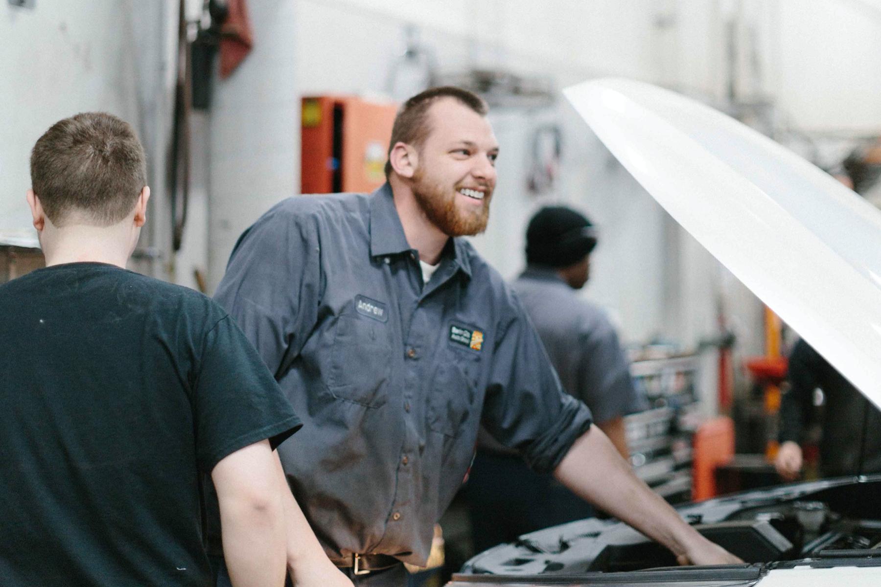 smiling service technician repairs car engine