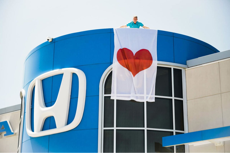 staff holds heart flag from dealership rooftop