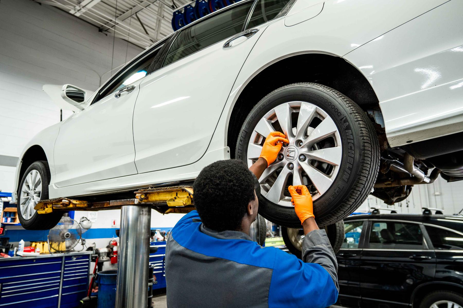 technician replaces car tire