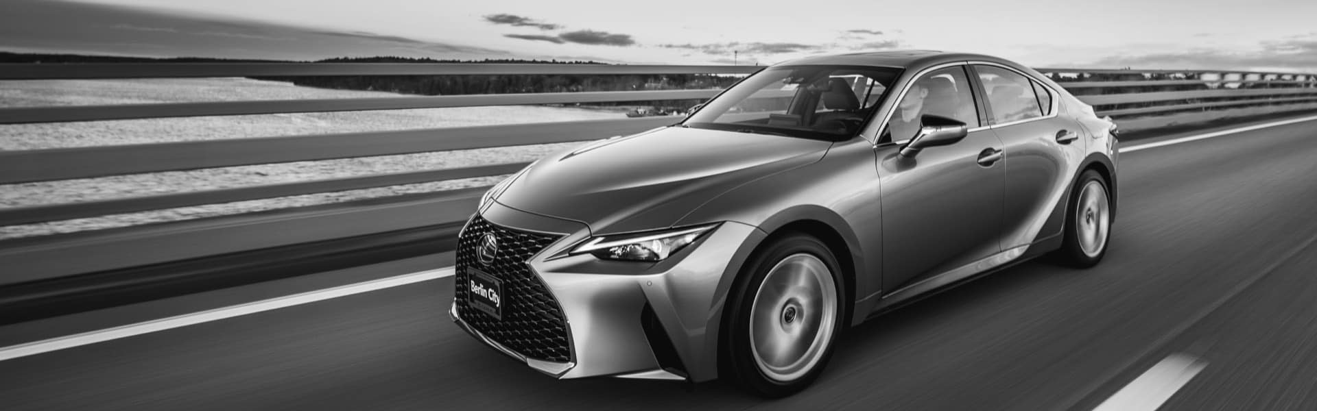 Black and white image of a Lexus Sedan driving on the coast