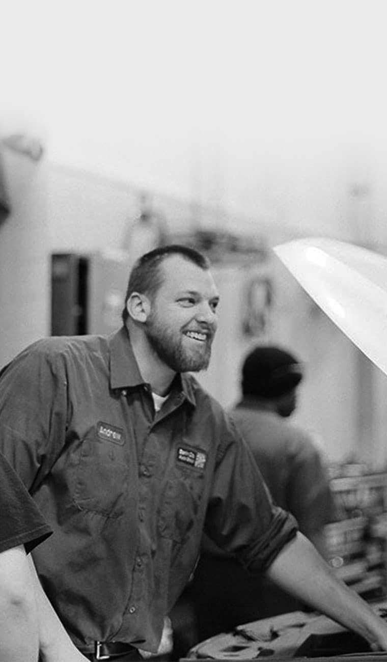 smiling technician looks up from under car engine hood
