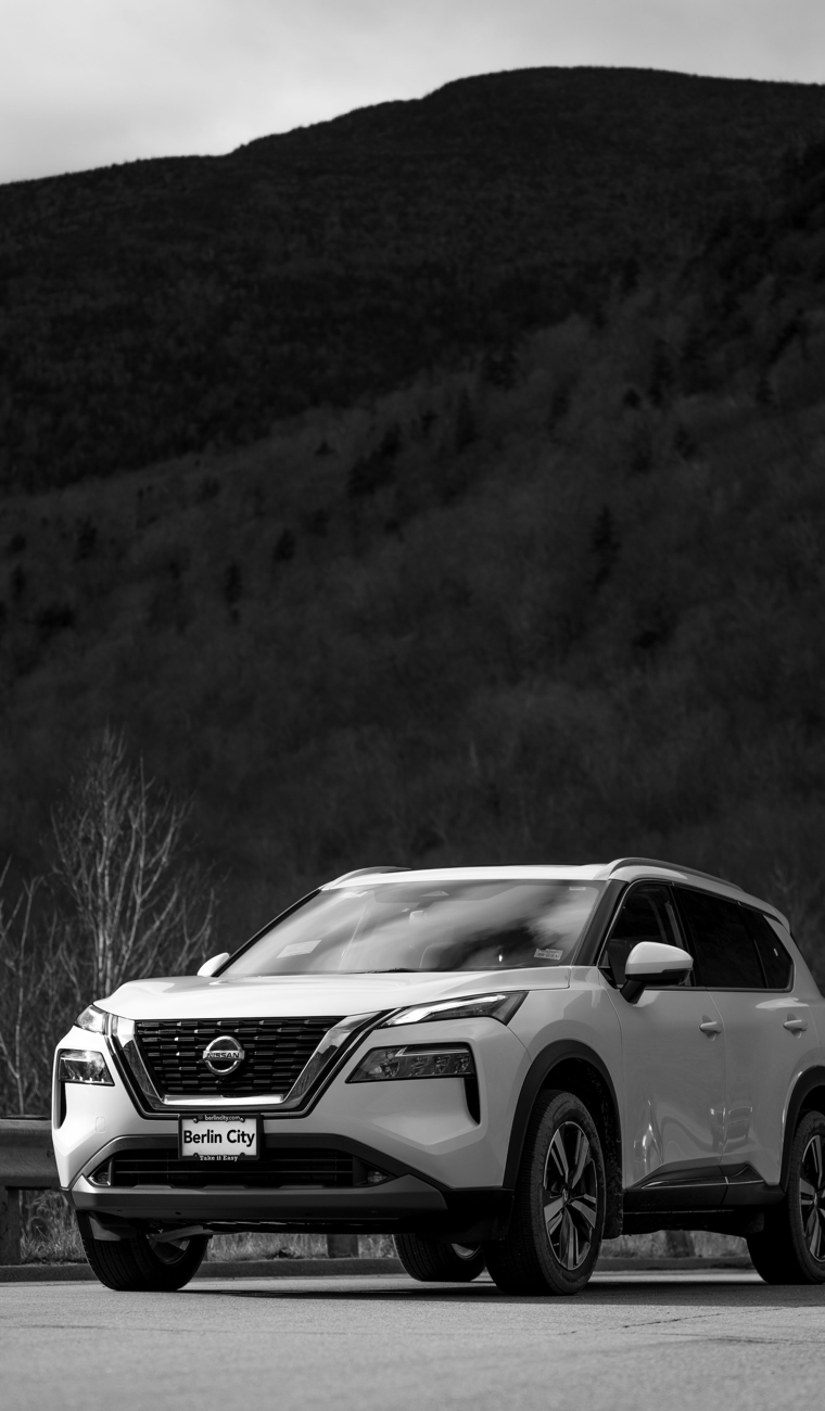 A white Nissan SUV driving with mountains behind
