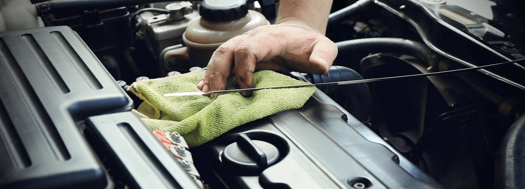 man checks oil level in car engine