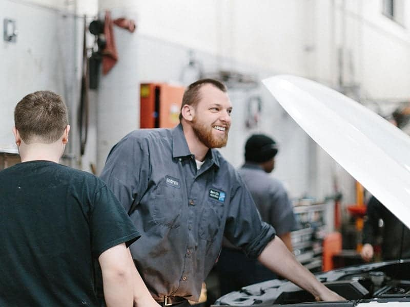 service technician smiles and looks up from under car hood