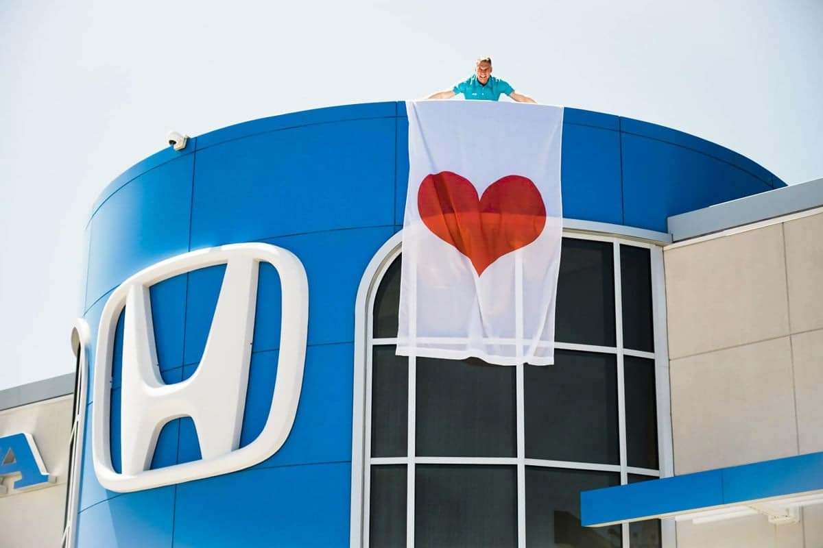 man holds heart flag on rooftop of dealership