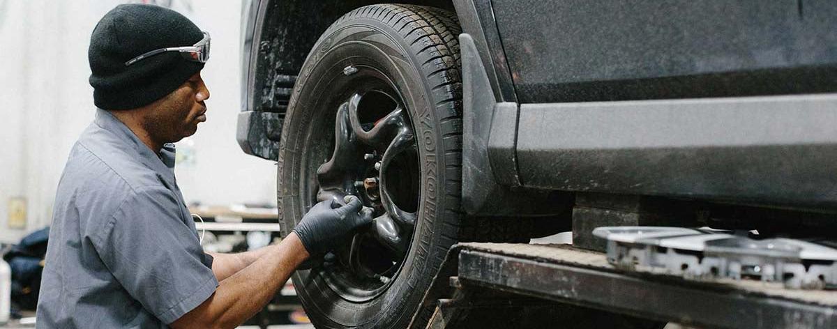 service technician replaces car tire on car jack