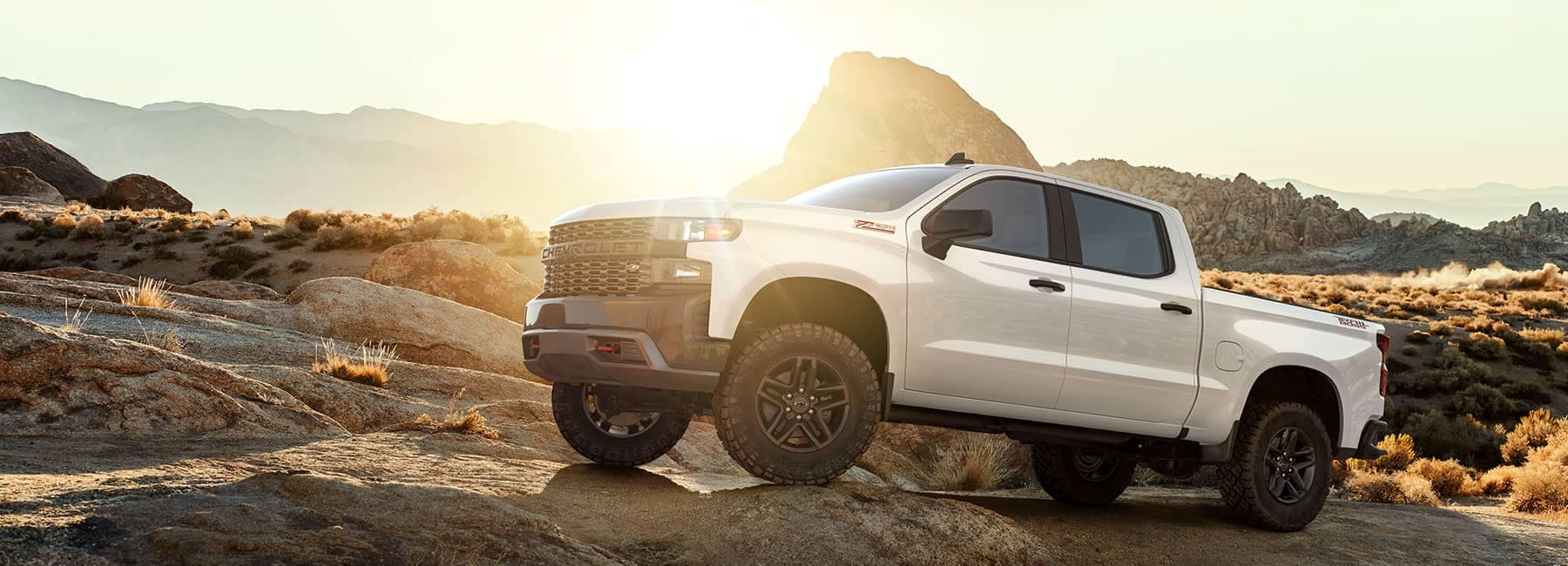 A White Chevy Silverado perched atop a boulder with the sun rising in the background
