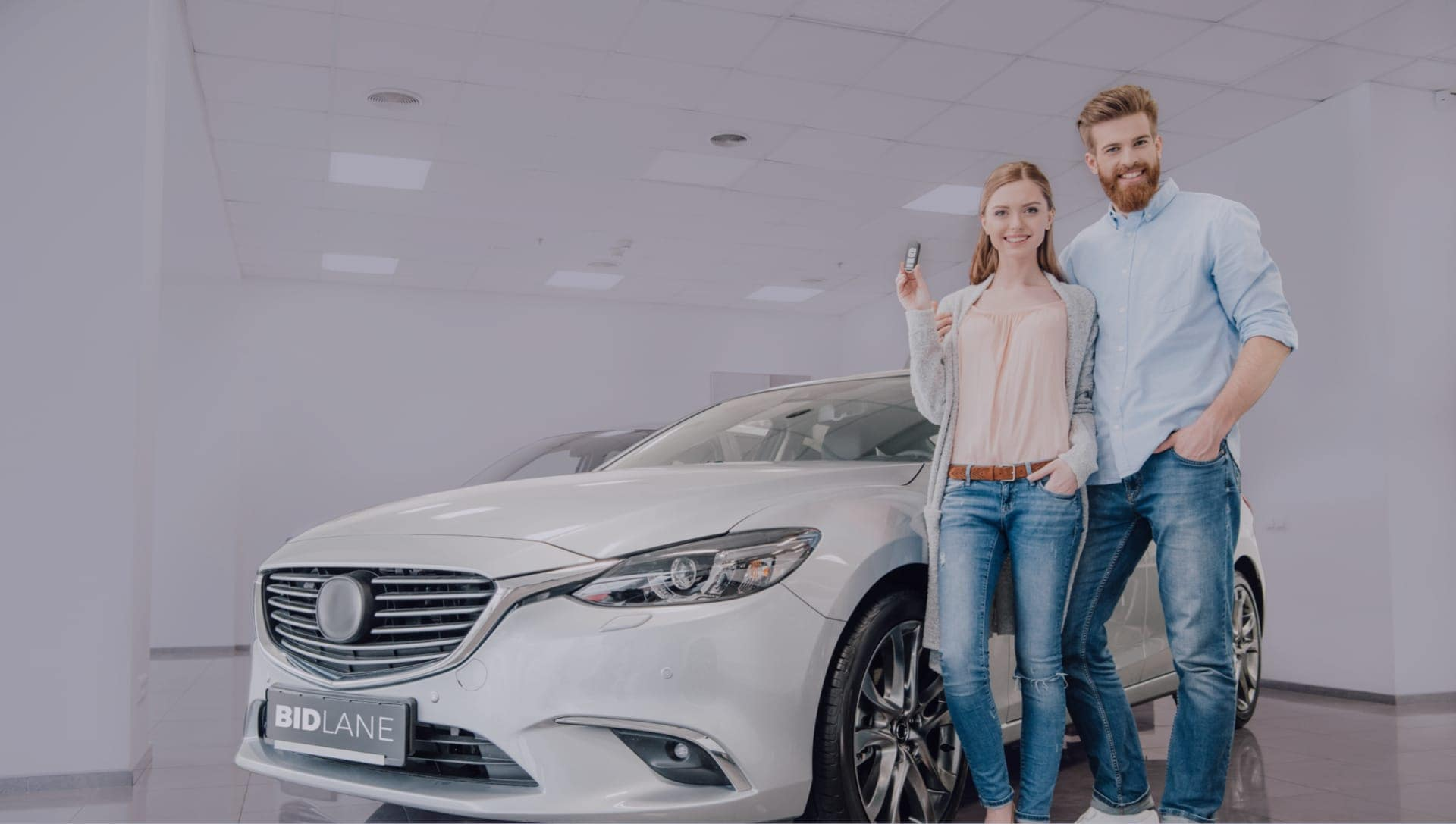 Couple Standing Next to White Sedan in showroom