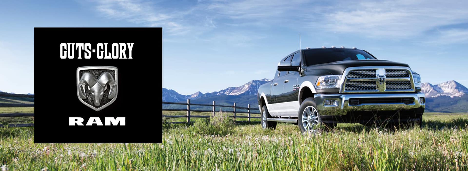 A Ram 1500 parked on farm land with mountains in the background.