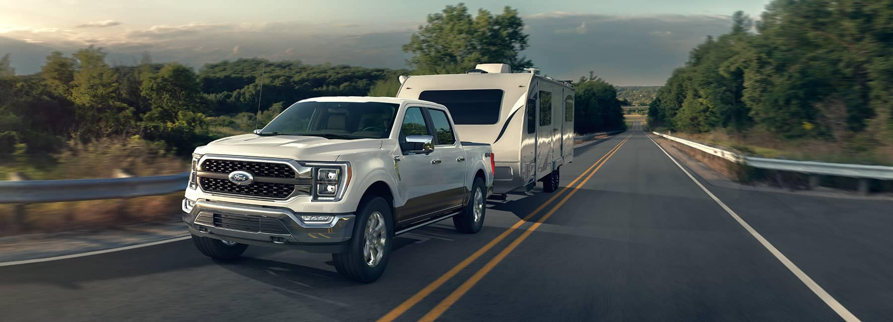 A white 2021 Ford 150 hauling an RV trailer along a mountain road