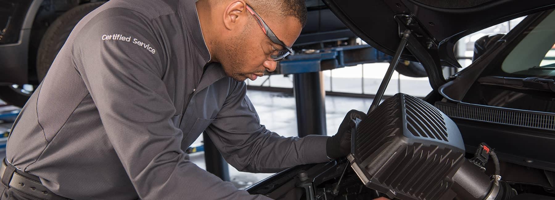 Certified technician inspects car engine
