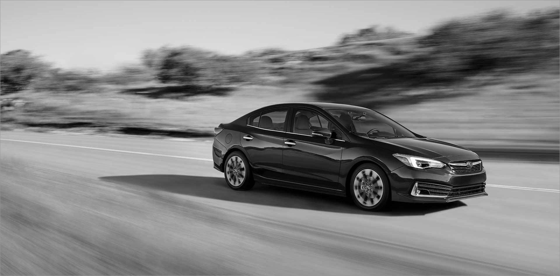 Grayscale Subaru Impreza drives on two lane country road