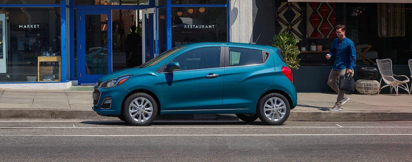 A man is walking towards a blue 2020 Chevy Spark that is parked in front of a restaurant.