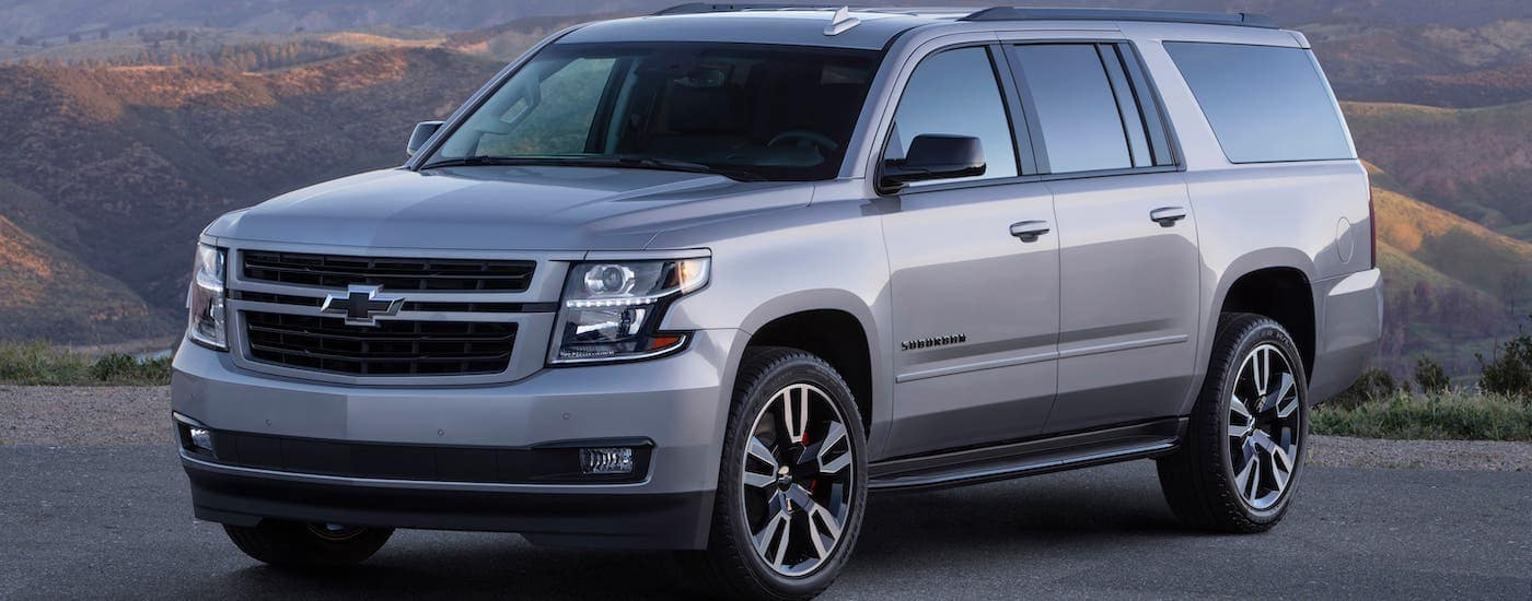 A silver 2020 Chevy Suburban RST is parked in a lot in front of mountains.