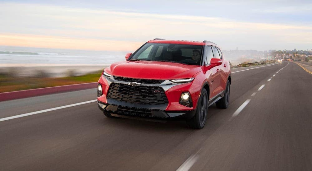 A red 2020 Chevy Blazer RS is driving along an ocean-side highway.