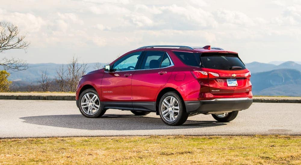 A red 2020 Chevy Equinox is parked in a lot overlooking mountains.