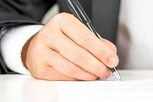 A hand signing a finance application