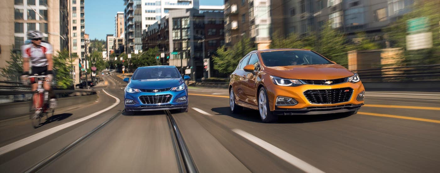 A blue 2018 Chevrolet Cruze sedan and orange Chevrolet Cruze Hatchback are driving on a city street next to someone on a bicycle.