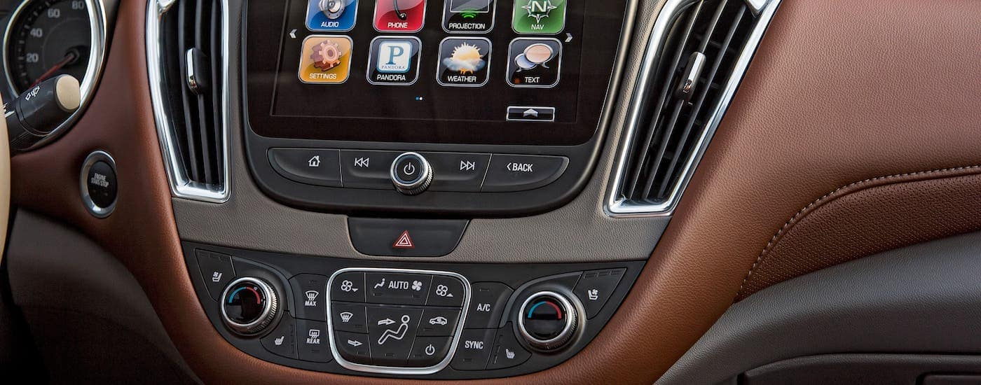 A closeup is shown of the infotainment screen and surrounding brown leather dashboard in a 2018 Chevrolet Malibu.