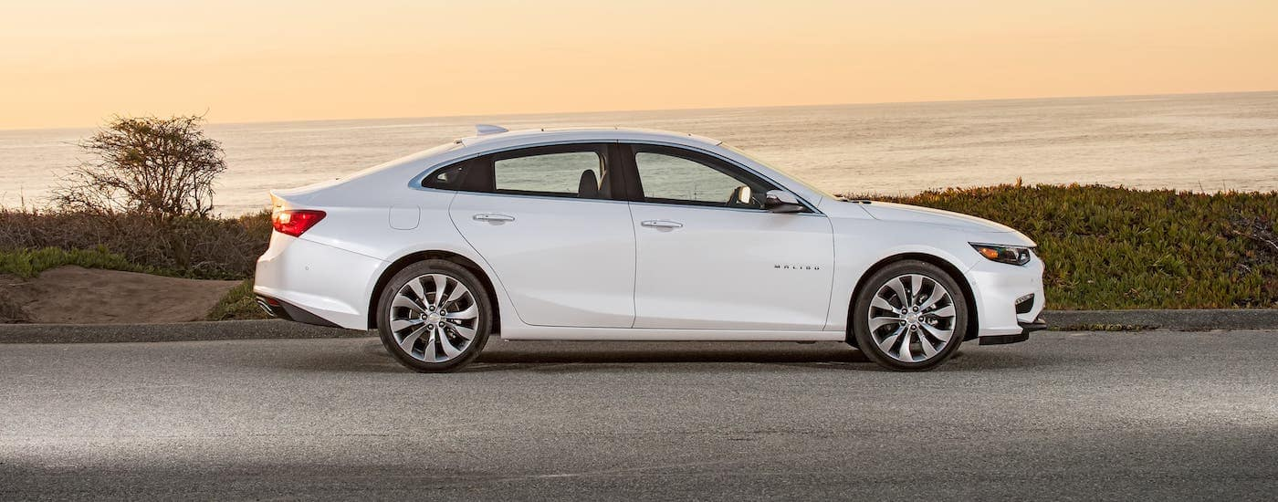 A white 2018 Chevrolet Malibu is parked in front of an ocean at sunset. Both the 2018 Chevrolet Cruze and 2018 Chevrolet Malibu can be found at your local Chevy dealer.