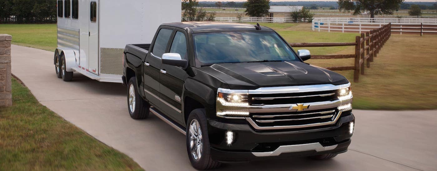 A black 2018 Chevrolet Silverado 1500 High Country is towing an enclosed trailer on a ranch.