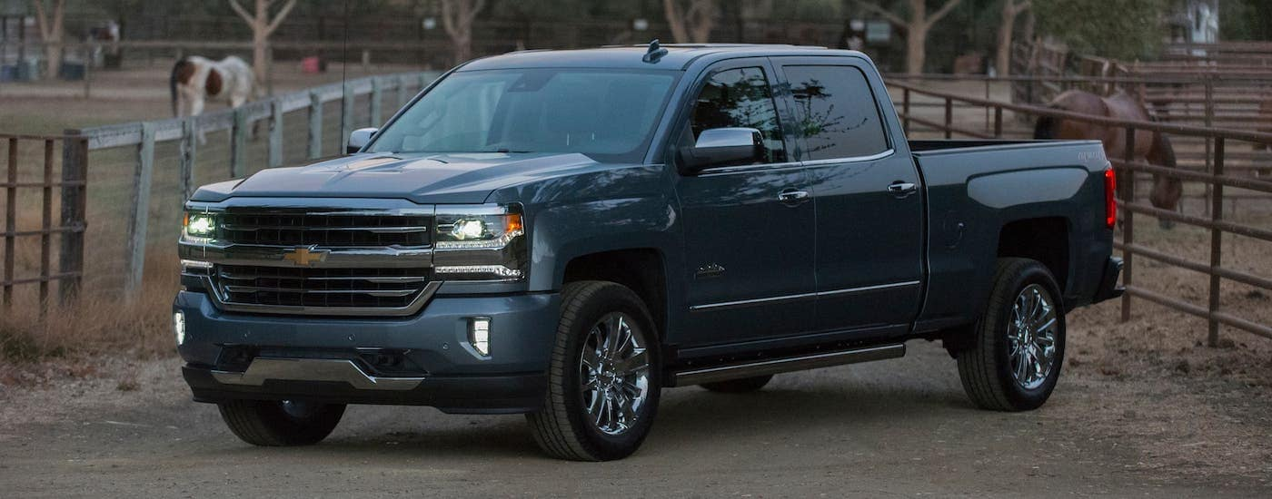 A blue 2018 Chevrolet Silverado 1500 High Country is parked in front of a ranch after winning over a Ram.