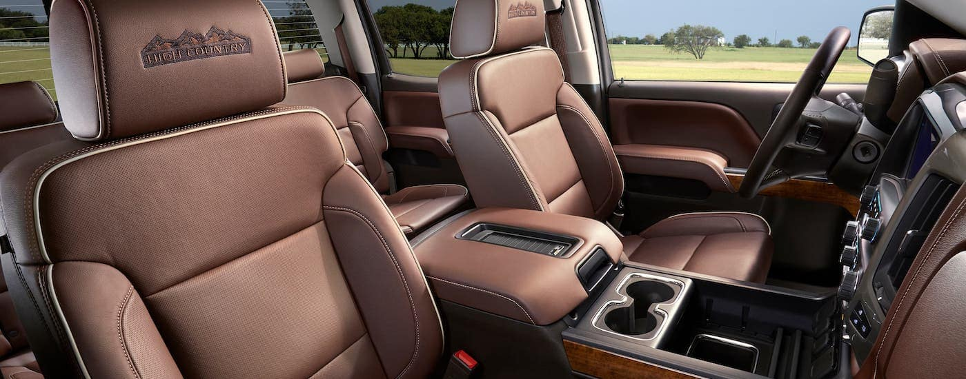 The luxurious brown leather interior of a 2018 Chevy Silverado High Country is shown.