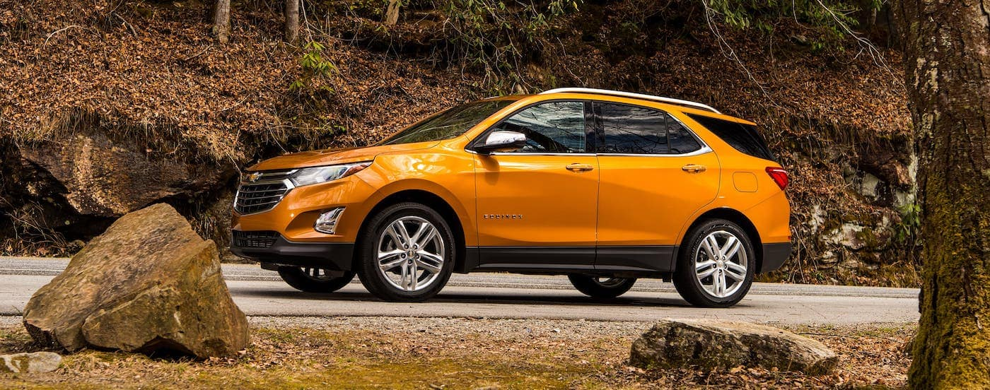 An orange 2019 Chevrolet Equinox is driving up a hill in fall.