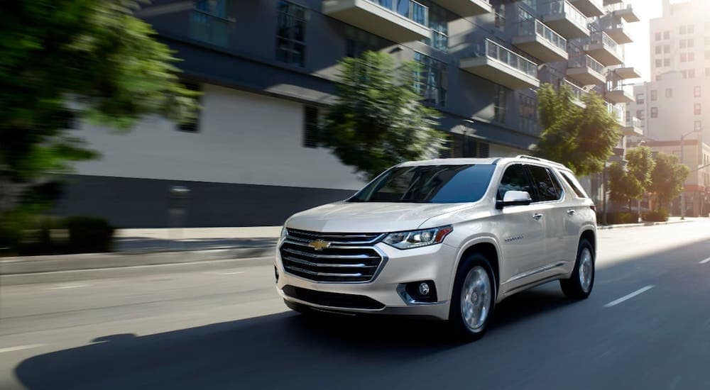 A white 2019 Chevrolet Traverse High Country is driving on a city street.