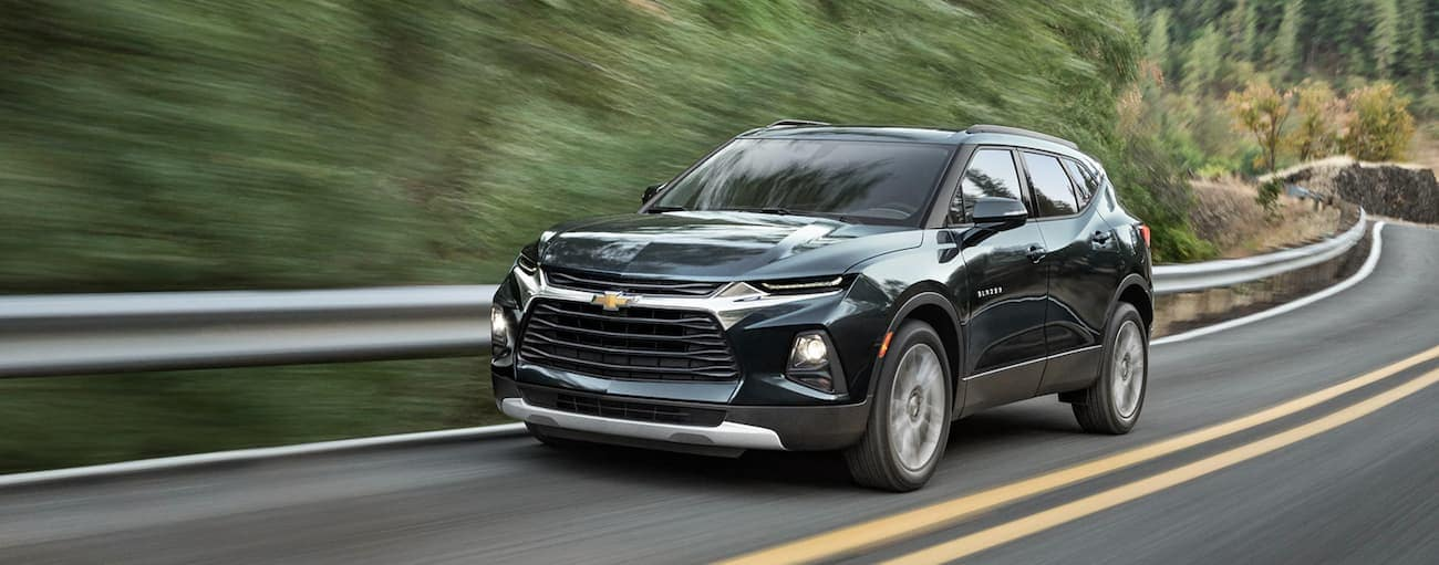 A dark green 2019 Chevy Blazer is driving on a winding tree-lined road after winning the 2019 Chevy Blazer vs 2019 Ford Edge comparison.