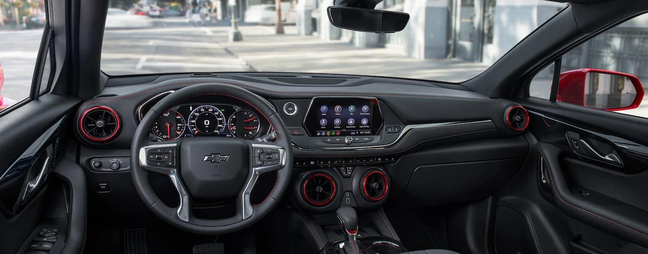 The black and red dashboard and infotainment features are shown.