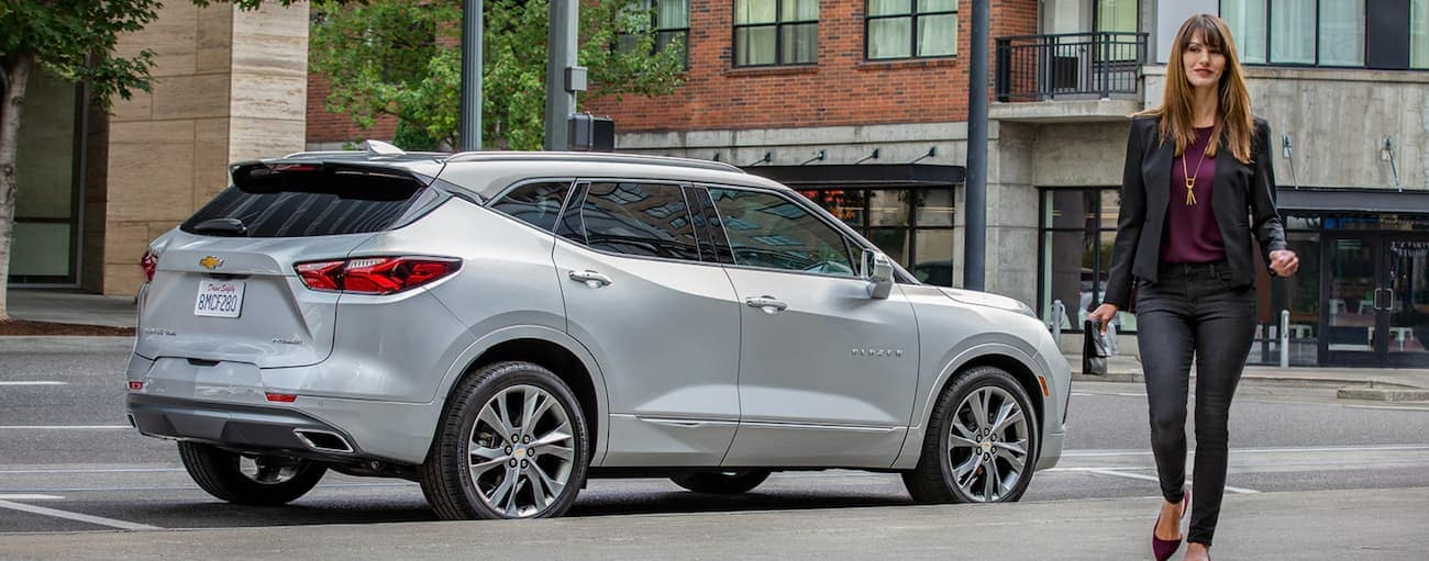 A woman is walking away from a silver 2019 Chevy Blazer on a city street in Indianapolis, IN.