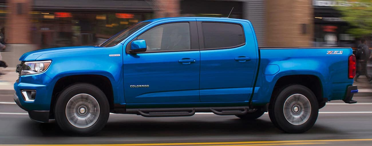 A blue 2019 Chevy Colorado is driving on a city street near Indianapolis, IN.